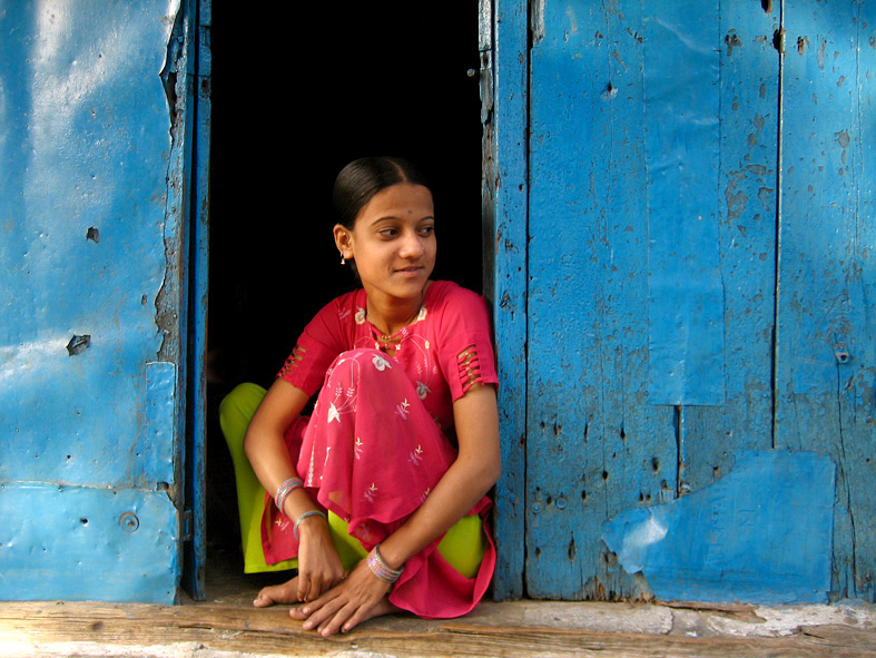 A young woman wearing a fuchsia-peach coloured kurta and salwar in an apple green shade is sitting on the precipice of her doorstep. The walls behind her painted a cornflower blue. Her hair is plaited and there is a slight smile on her face.