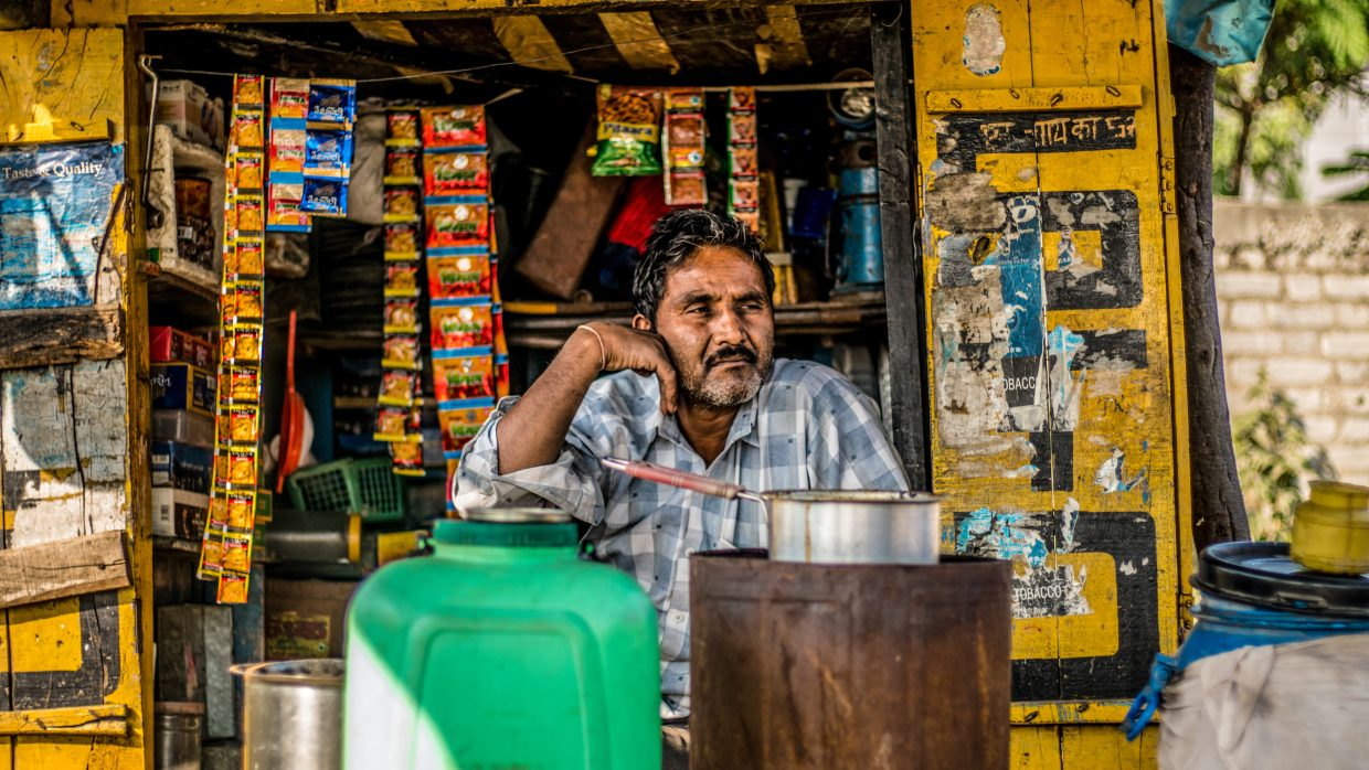A man is sitting in his tea shop with a forlorn expression. A huge iron tea canister, green plastic bucket and other wares are seen in the surrounding.